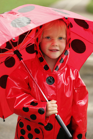 A child with matching raincoat and umbrella photo