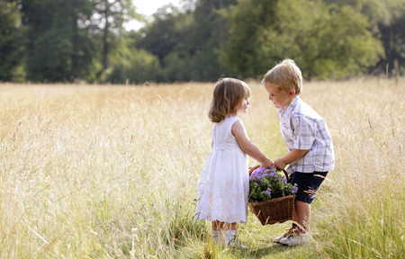 Little boy helping little girl with the basket of flowers photo