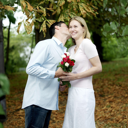 Man giving his girlfriend a peck on the cheek after presenting her with flowers photo