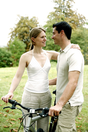 Couple and a bicycle in the park photo