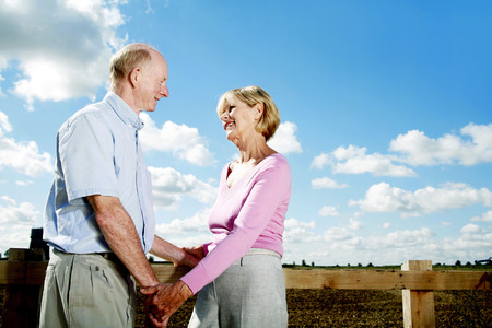Senior couple holding hands while looking at each other photo