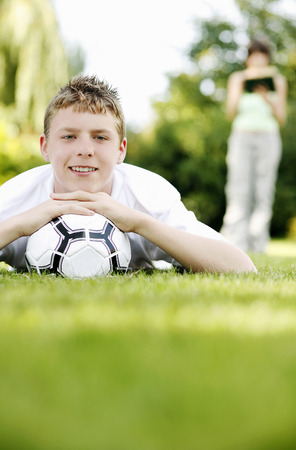 Boy lying forward on the grass with his chin resting on a soccer ball Stock Photo