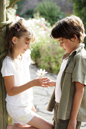 Boy giving flower to girl photo