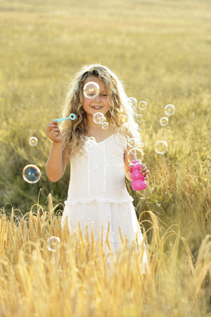 Girl blowing bubbles in the field photo