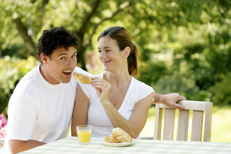 Woman feeding her boyfriend croissant photo