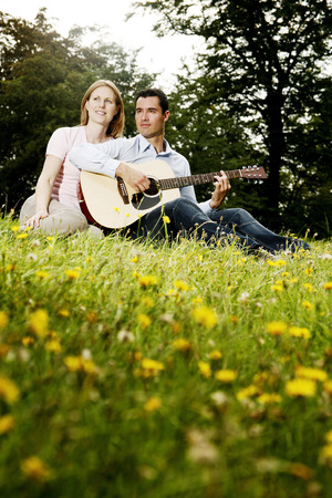 Man playing guitar for his girlfriend while sitting in the park photo
