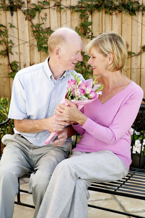 Senior man giving his wife a bouquet of flowers photo