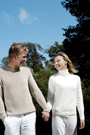holding hands while walking: Couple holding hands while walking in the park Stock Photo