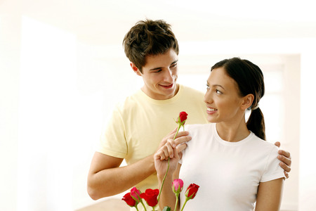 Woman looking at her boyfriend while holding a rose Stock Photo - 26204566