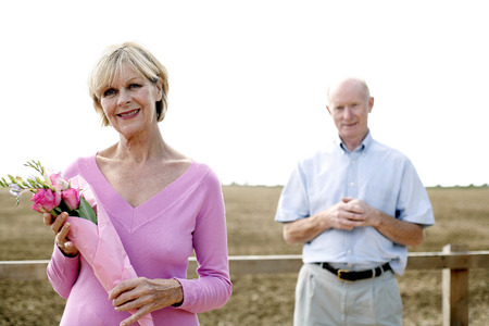 Senior woman holding a bouquet of flowers with her husband standing behind her photo