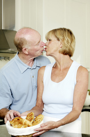 Senior couple kissing in the kitchen photo