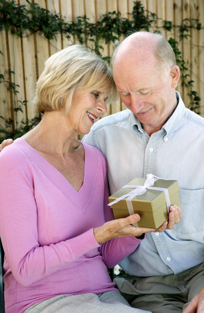 Senior woman getting a present from her husband photo
