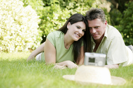 lying forward: Couple lying forward on the grass smiling at the digital camera Stock Photo