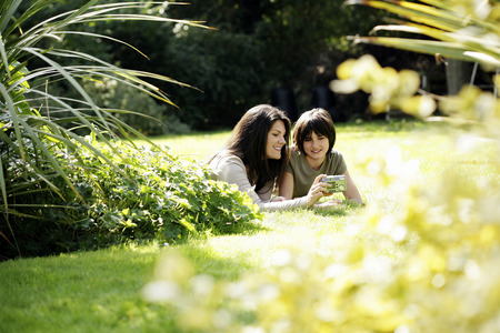 lying forward: Mother and daughter taking picture together Stock Photo