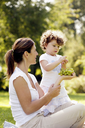 Girl taking a green grape from her mother photo