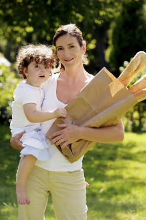 Woman holding a paper bag of french breads while carrying her daughter photo