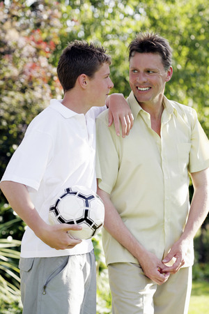 Boy holding soccer ball while talking to his father photo