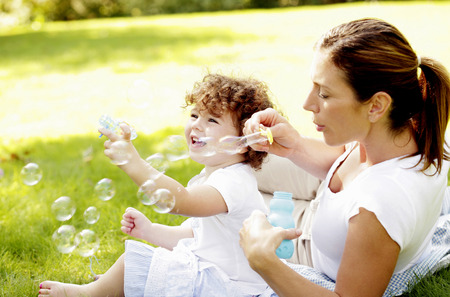 Mother and daughter playing with soap bubbles photo