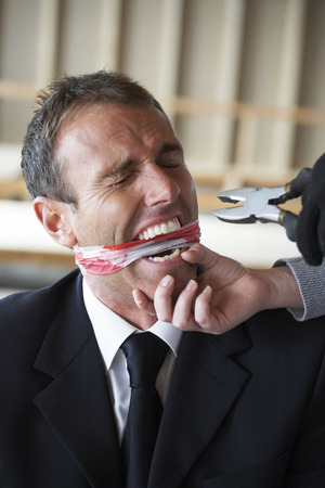 Kidnapper threatening businessman with pliers Stock Photo