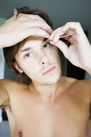 tweezing eyebrow: Man grooming his eyebrow