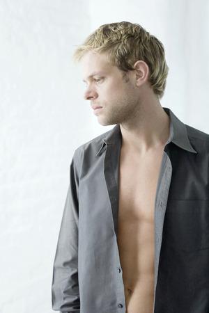 unbuttoned: Man with unbuttoned shirt thinking Stock Photo