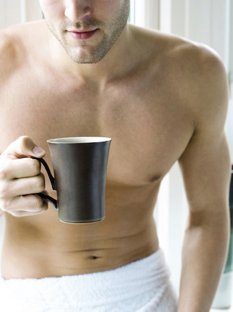 Man with towel holding a cup of coffee photo