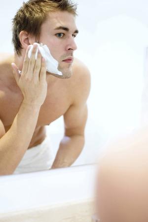 Man applying shaving cream on his face photo