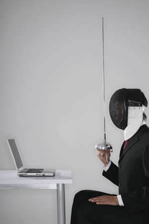 quarter foil: Businessman with a fencing foil and fencing mask looking at a laptop