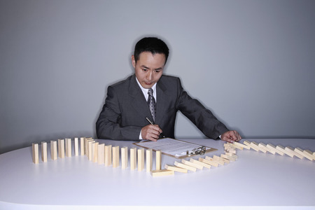 Businessman examining wooden blocks on the table photo