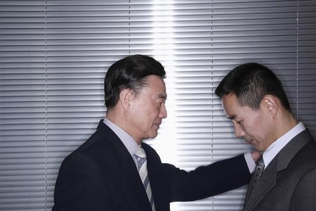 Businessman putting his hand on his subordinate