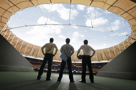 looked: Three businessmen standing at the stadium