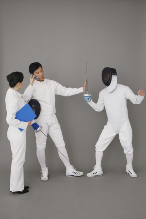 Businesswoman holding a mobile phone for a man while he stops the fencing competition Stock Photo - 26204948
