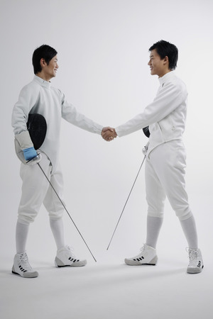Two men in fencing suits shaking hands photo