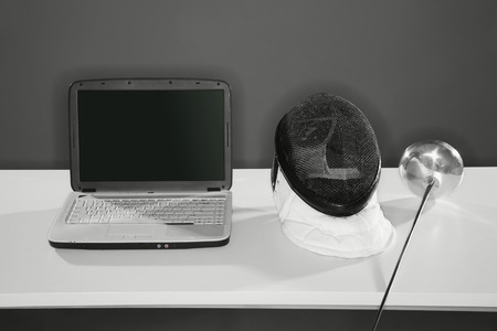 fencing foil: Laptop with fencing mask and foil on the table