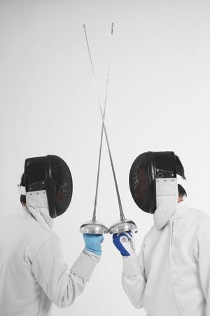 esgrima: Dos hombres vestidos con trajes de esgrima en un duelo