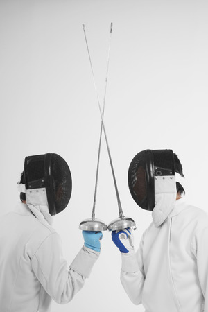 fencing foil: Two men in fencing suits in a duel