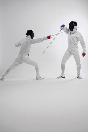 dueling: Two men in fencing suits dueling