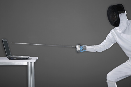 fencing foil: Man in fencing suit aiming fencing foil at a laptop Stock Photo