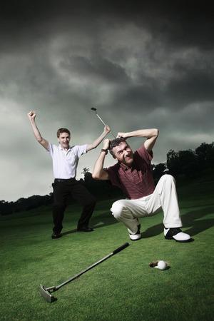 jubilating: Men playing golf at golf course Stock Photo