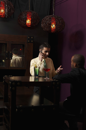 Businessmen having discussion over glasses of cocktails photo