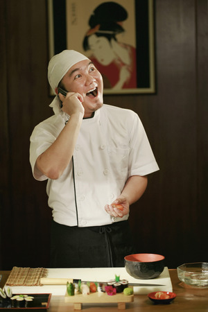 Chef talking on the phone while preparing food photo