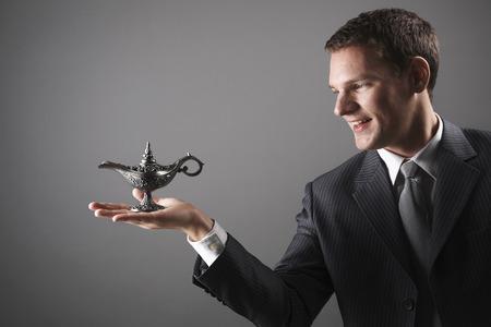 lampe magique: Businessman holding lampe magique Banque d'images