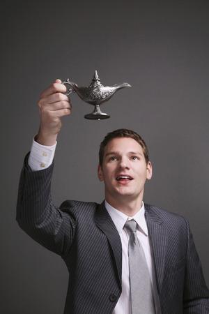 lampe magique: Businessman holding up lampe magique Banque d'images