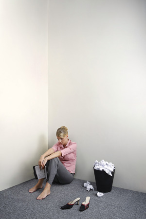 overflows: Businesswoman sitting on the floor holding organizer, a dustbin full of crumpled paper balls beside her Stock Photo