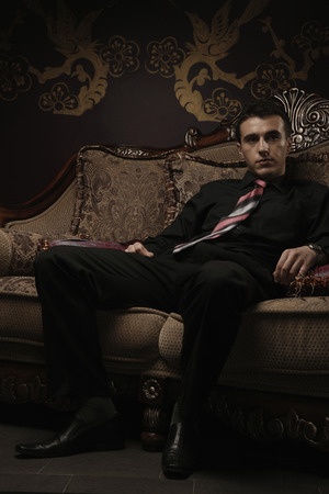 Businessman sitting on antique sofa photo