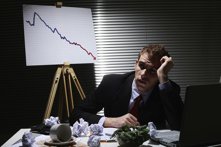 frowns: Businessman frowning with crumpled paper balls on the table