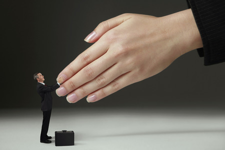 Businessman shaking hands with giant sized hands photo