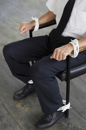 Businessman being tied to a chair photo