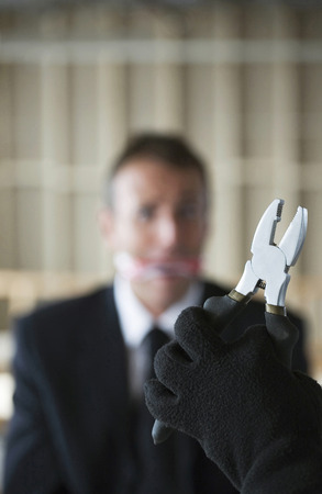 Hand holding pliers with gagged businessman looking at it photo