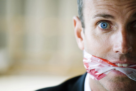 Terrified looking man with gagged mouth photo